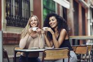 Two happy friends drinking coffee in sidewalk cafe - JSMF00050