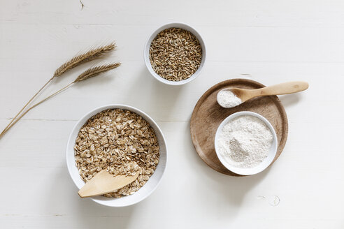 Rye ears and bowls of rye flakes, rye flour and rye grains on white background - EVGF03291