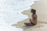 Indonesia, Bali, young woman sitting on the beach - KNTF01057