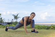 Indonesia, Bali, woman stretching - KNTF01063