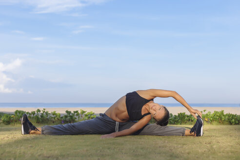 Indonesia, Bali, woman stretching - KNTF01069