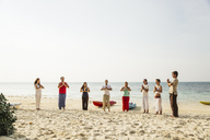 Thailand, Koh Phangan, group of people doing yoga on a beach - MOMF00380