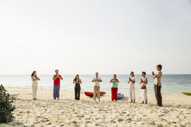 Thailand, Koh Phangan, group of people doing yoga on a beach - MOMF00380