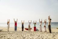 Thailand, Koh Phangan, group of people doing yoga on a beach - MOMF00383
