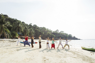 Thailand, Koh Phangan, group of people doing yoga on a beach - MOMF00386