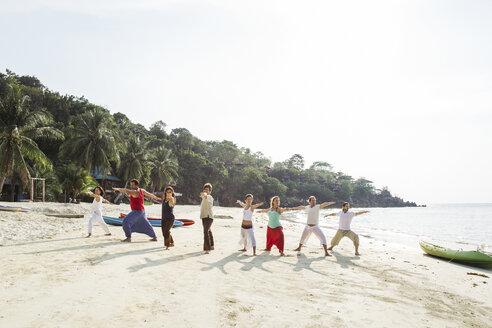 Thailand, Koh Phangan, group of people doing yoga on a beach - MOMF00386
