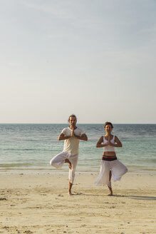 Thailand, Koh Phangan, couple doing yoga on a beach - MOMF00389