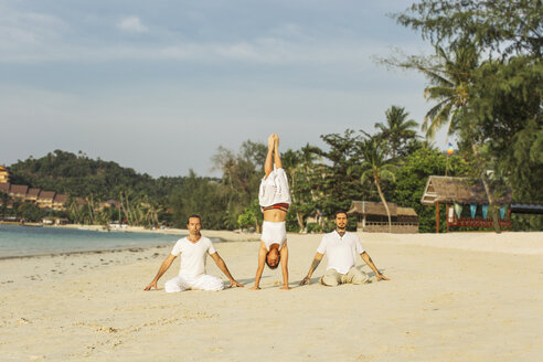 Thailand, Koh Phangan, three people doing yoga on a beach - MOMF00392