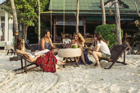 Thailand, Koh Phangan, friends having fun in a cafe at the beach - MOMF00398