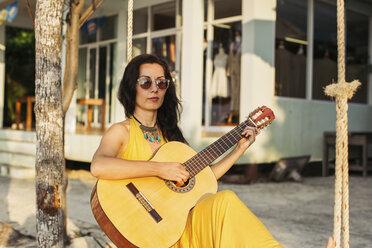 Thailand, Koh Phangan, woman playing guitar at the beach - MOMF00401