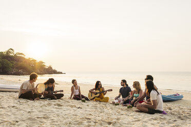 Thailand, Koh Phangan, group of people sitting on a beach with guitar at sunset - MOMF00404
