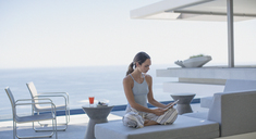 Woman in pajamas using digital tablet on modern, luxury home showcase exterior patio with ocean view - HOXF01035