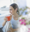 Smiling brunette woman in pajamas drinking juice - HOXF01038