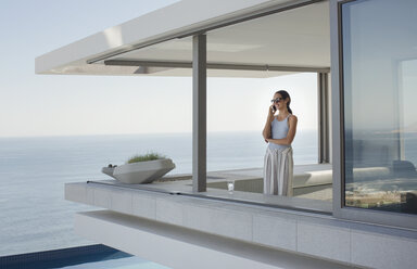 Woman talking on cell phone on modern, luxury home showcase exterior patio with ocean view - HOXF01044