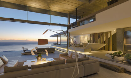 Illuminated modern, luxury home showcase interior living room with ocean view at dusk - HOXF01068
