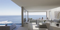 Woman relaxing on modern, luxury home showcase patio with sunny ocean view - HOXF01074