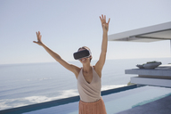 Energetic woman using virtual reality simulator glasses on modern, luxury home showcase exterior patio with ocean view - HOXF01083
