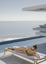 Woman sunbathing, texting with smart phone on lounge chair on sunny luxury patio with ocean view - HOXF01086