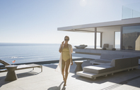 Woman in bathing suit walking on sunny modern, luxury home showcase exterior patio with ocean view - HOXF01089