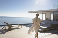 Woman walking on sunny modern, luxury home showcase exterior patio with ocean view - HOXF01095