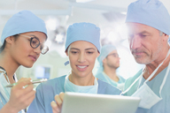 Surgeons using digital tablet in operating room - HOXF01116