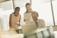 Business people working at laptop in sunny office - HOXF01137