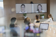 Business people talking on monitors in video conference - HOXF01140