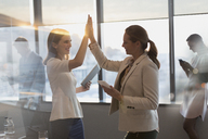 Businesswomen with digital tablets high-fiving in conference room - HOXF01161