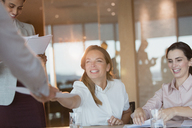 Smiling businesswoman handing paperwork to colleague in conference room meeting - HOXF01167