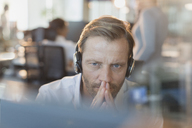 Serious businessman wearing headphones, working at computer - HOXF01194