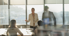 Businesswoman talking, leading meeting in sunny conference room - HOXF01206