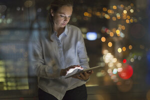 Businesswoman working late at digital tablet in office at night - HOXF01245