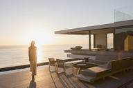Woman walking on modern, luxury home showcase exterior deck with sunset ocean view - HOXF01251