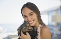 Portrait smiling woman cuddling small dog - HOXF01257