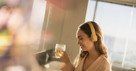 Smiling woman with headphones listening to music and drinking - HOXF01266