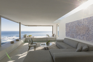 Sunny modern, luxury home showcase interior living room with ocean view - HOXF01269