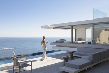 Woman on sunny modern, luxury home showcase exterior patio with ocean view - HOXF01272