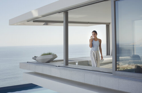 Woman talking on cell phone on modern, luxury home showcase exterior patio with ocean view - HOXF01275