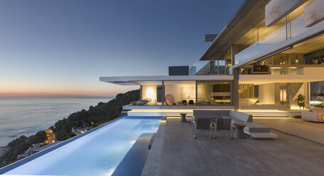 Illuminated modern, luxury home showcase exterior patio with lap pool and ocean view at twilight - HOXF01281