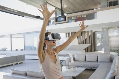 Energetic woman using virtual reality simulator glasses with arms raised in modern, luxury home showcase living room - HOXF01284