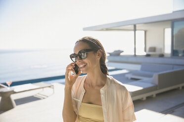 Smiling woman talking on smart phone on sunny modern, luxury home showcase exterior patio - HOXF01287
