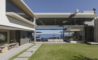 Sunny modern, luxury home showcase exterior courtyard and house - HOXF01293