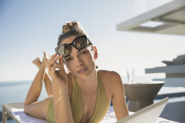 Portrait serious, confident woman in bathing suit and sunglasses sunbathing with digital tablet on sunny luxury patio - HOXF01296