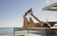 Woman sunbathing, using digital tablet on lounge chair on sunny patio - HOXF01314