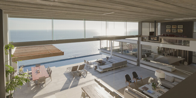 Elevated view modern, luxury home showcase interior living room and patio with sunny ocean view - HOXF01323