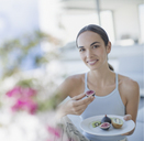 Portrait smiling brunette woman eating figs and kiwi - HOXF01326