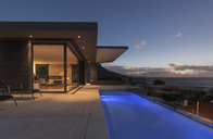 Tranquil blue lap swimming pool outside modern luxury home showcase exterior at dusk - HOXF01338