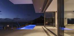Illuminated blue lap swimming pool outside modern luxury home showcase exterior at night - HOXF01341