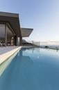 Tranquil blue lap swimming pool outside modern luxury home showcase exterior - HOXF01344
