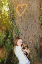 Girl holding puppy dog below tree with heart-shape - HOXF01386